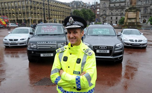Deputy Chief Constable Campbell Corrigan in front of the 'seized' cars